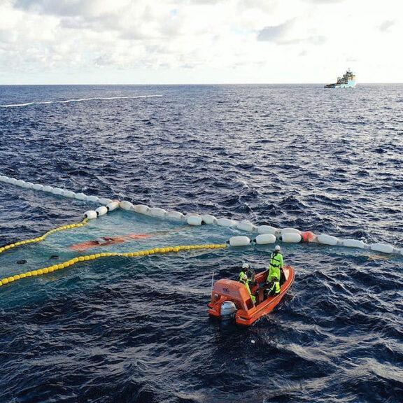 Linha é puxada por  dois barcos, formando uma espécie de funil para uma grande rede que armazena o plástico flutuante